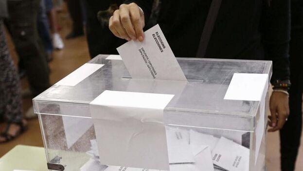 Un votante coloca un sobre en una urna durante las elecciones en Barcelona. (EFE)