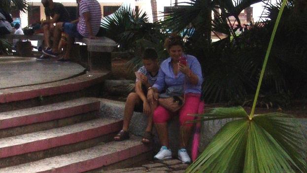 Familias enteras se conectan al wifi en el centro de Pinar del Río. (14ymedio)