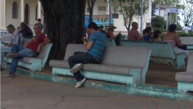 9 Joven conectado por su móvil al wifi del Parque de la Independencia, en Pinar del Río. (14ymedio)