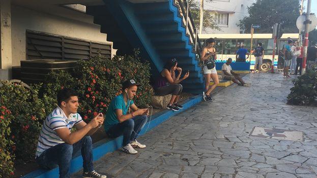 Jóvenes conectados en el punto wifi de La Rampa, en La Habana. (14ymedio)