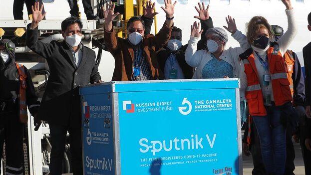 El presidente de Boliva, Luis Arce, saluda junto a un contenedor con dosis de la vacuna rusa Sputnik V, en el Aeropuerto Internacional de El Alto, Bolivia. (EFE/Martin Alipaz)