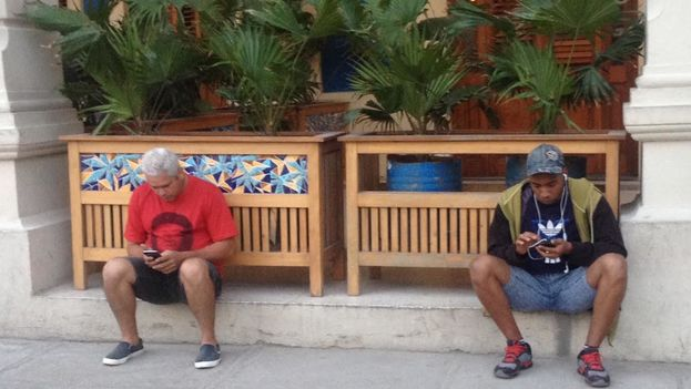 Un turista lleva una camiseta con el rostro del Che Guevara en La Habana, mientras un cubano exhibe otra con el logotipo de Adidas. (14ymedio)