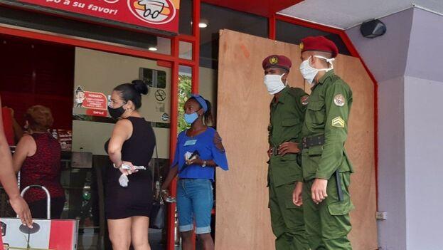 """Dos """"boinas rojas"""" custodiando en las afueras de la Plaza Comercial Carlos III, en Centro Habana. (14ymedio)"""