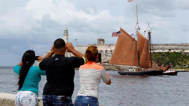 Cubanos fotografían la llegada a La Habana de la embarcación estadounidense 'Roseway', construida en 1925. (EFE/Ernesto Mastrascusa)