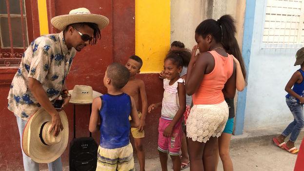 Debido al calor, los miembros de ReConstrucción reparten sombreros entre los que se acercan a escuchar la banda sonora de Casamayor. (14ymedio)