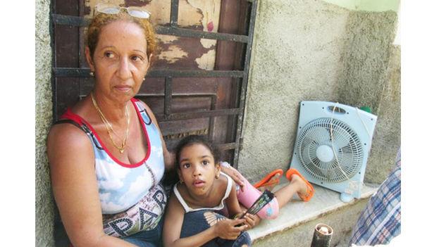 Dionisia Rodríguez Cedeño junto a una de sus nietas, asegura que prefiere dormir en la calle ante el temor de que el techo de su vivienda siga desplomándose. (14ymedio)