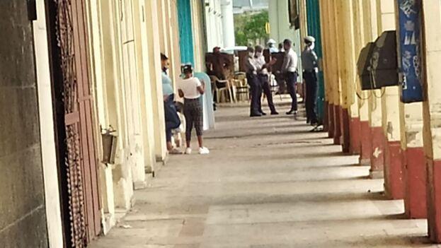Elementos policiales que permanecen frente al edificio. (14ymedio)