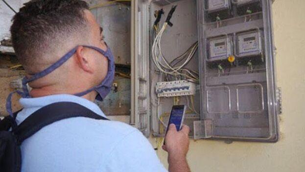 Un trabajador de la Empresa Eléctrica revisa los metro contadores de un edificio. (Tv Avileña)