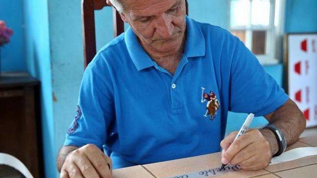 Fotografía fechada el 23 de mayo de 2018 que muestra al informático Carlos Parra mientras escribe en la cinta de una corona de flores durante una entrevista en la provincia de Holguín . (EFE)