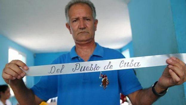 Fotografía fechada el 23 de mayo de 2018 que muestra al informático Carlos Parra mientras exhibe la cinta de una corona de flores escrita manualmente por él, durante una entrevista en la provincia de Holguín. (EFE)