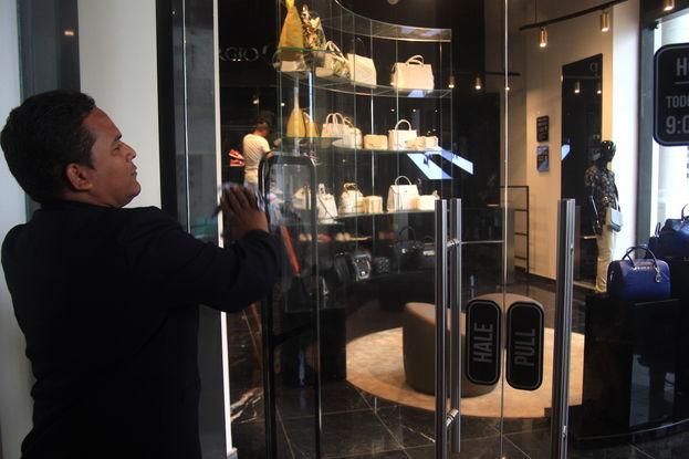 """El empleado que cuida la puerta de la boutique advierte que """"no se pueden hacer fotos"""" ni tener """"la wifi encendida"""" en el teléfono. (14ymedio)"""