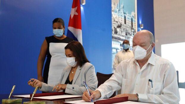 Firma de acuerdo de cooperación entre Rodrigo Malmierca, ministro cubano de Comercio Exterior e Inversión Extranjera, y Elba Rosa Pérez Montoya, ministra de Ciencia, Tecnología y Medio Ambiente, durante la inauguración de la Ventanilla Única de Inversión Extranjera, en La Habana. (EFE/Yander Zamora)