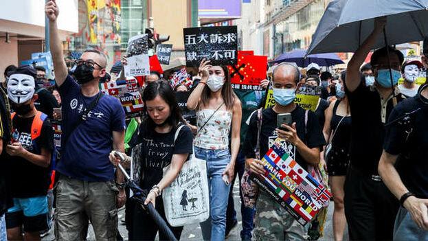 Más de un millar de personas retaron con sus máscaras la decisión de la Jefa del Ejecutivo, Carrie Lam, de invocar una ordenanza de la época británica para aprobar su ley. (EFE)
