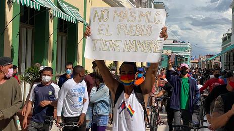 Joven con pancarta durante las protestas del 11 de julio en Cuba. (Captura)