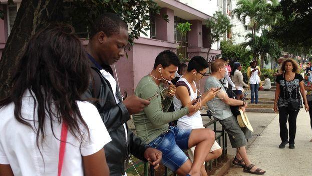 Jóvenes utilizan sus teléfonos celulares para conectarse a la red wifi en La Habana. (14ymedio)