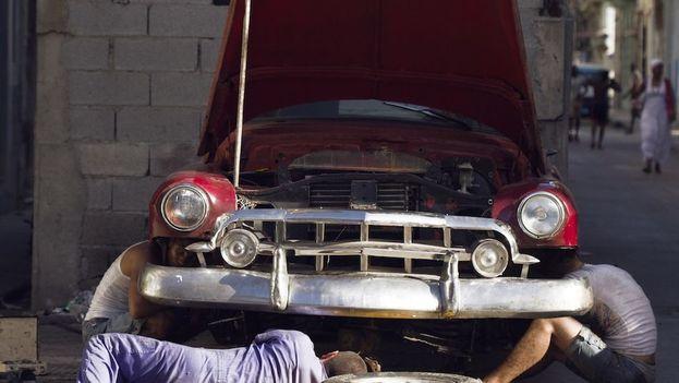 Mecánicos cubanos chapistean un auto. (Archivo 14ymedio)