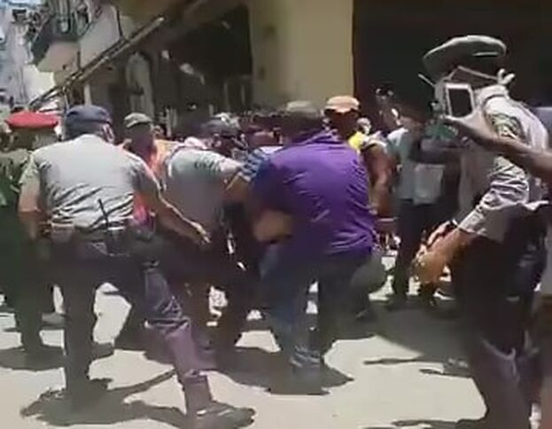 Momento en que las fuerzas represoras intentan llevarse detenidos a algunos de los activistas. (Captura)
