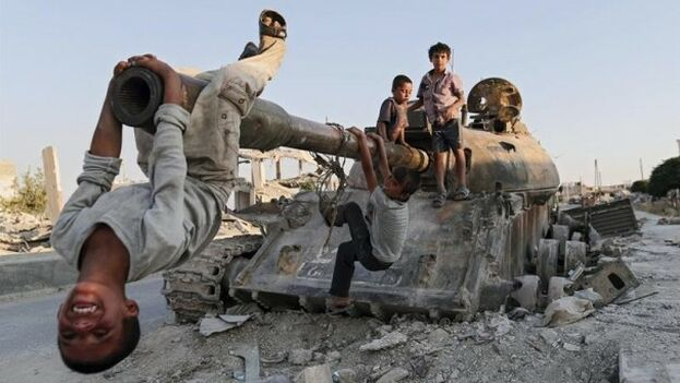 Niños sirios juegan con un tanque destruido en la ciudad de Kobani. (EFE)
