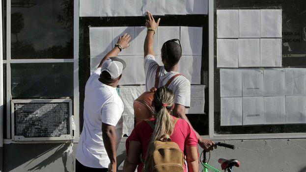 Los migrantes cubanos verifican su estado en la lista publicada en la entrada al Puente Internacional en Matamoros, México. (el Nuevo Herald)