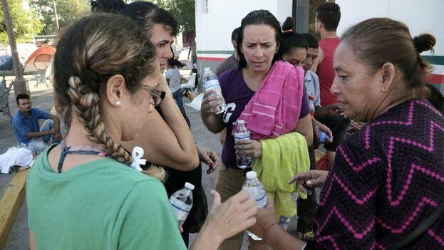Una voluntaria mexicana, a la derecha, da agua a mujeres migrantes cubanas que viven en un campamento improvisado junto al Puente Internacional en Matamoros, México. (el Nuevo Herald)