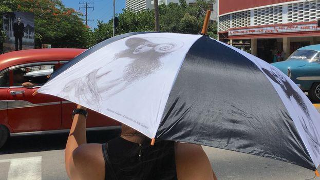 Una mujer se pasea por la Rampa habanera con una sombrilla de la red de tiendas Artex. (14ymedio)