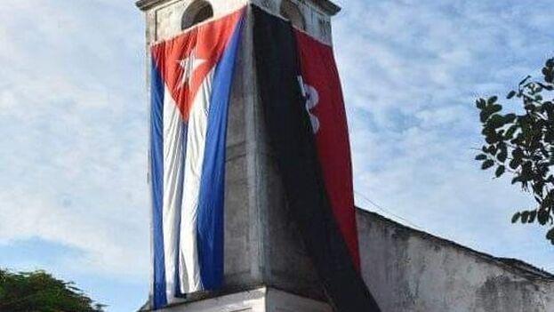 Durante el evento conmemorativo por el oficialista Día de la Rebeldía, la iglesia de Corralillo fue ataviada con dos gigantestas banderas: la enseña nacional y la alusiva al Movimiento surgido tras el ataque al Cuartel Moncada. (Facebook)