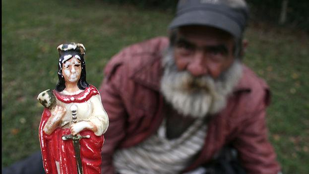 Un hombre muestra una imagen de Santa Bárbara que se sincretiza con Changó en la santería cubana. (Flickr/Priscilla Mora)