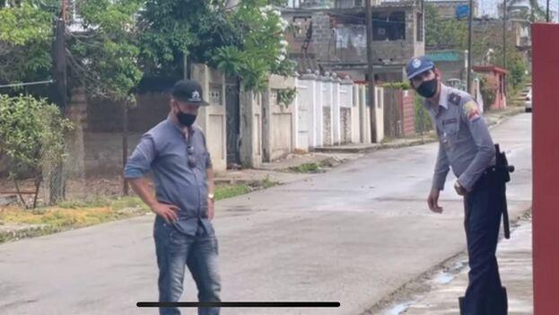 Un policía y un agente de la Seguridad del Estado vigilan las inmediaciones de la casa de Iliana Hernández, en Cojímar, La Habana. (Captura)