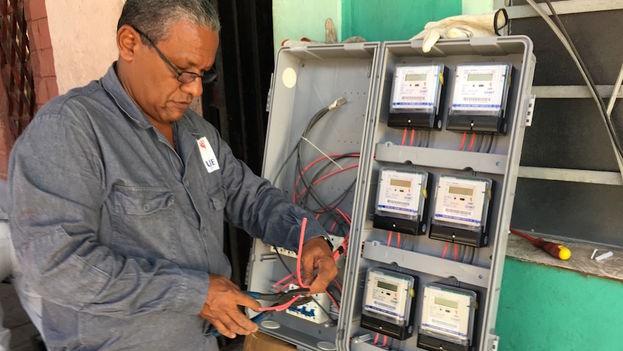 Un empleado de la Unión Eléctrica de Cuba cambia los metros contadores en un edificio de La Habana. (14ymedio)