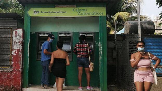 Varias personas en La Habana intentando retirar dinero de tres cajeros que pertenecen al Banco Metropolitano. (14ymedio)