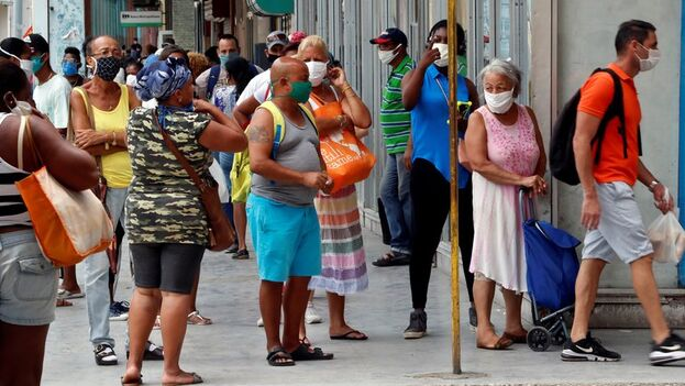 Varias personas con tapabocas mientras hacen cola afuera de un centro comercial, en La Habana. (EFE/Ernesto Mastrascusa/Archivo