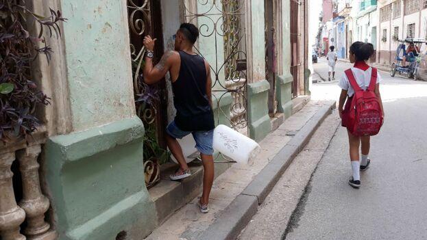 Vecinos cargados con galones vacíos se acercan en busca de agua en San Isidro, en La Habana Vieja. (14ymedio)