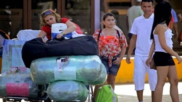 Viajeros cubanos llegan al aeropuerto internacional de La Habana cargados de bultos. (EFE)