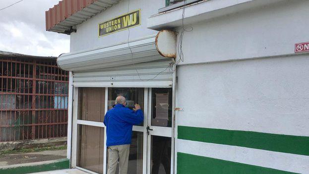 Un cliente mira a través del cristal de una sucursal de Western Union en La Habana para averiguar si puede cobrar en efectivo una remesa. (14yemdio)