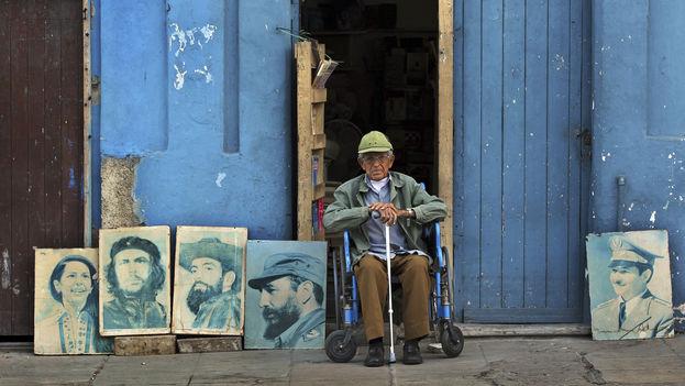 Un anciano posa junto a una serie de retratos de líderes cubanos. (EFE)