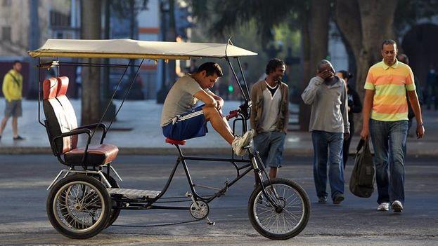 Un hombre espera en su 'bicitaxi' algún cliente para recorrer las calles de La Habana. (EFE)