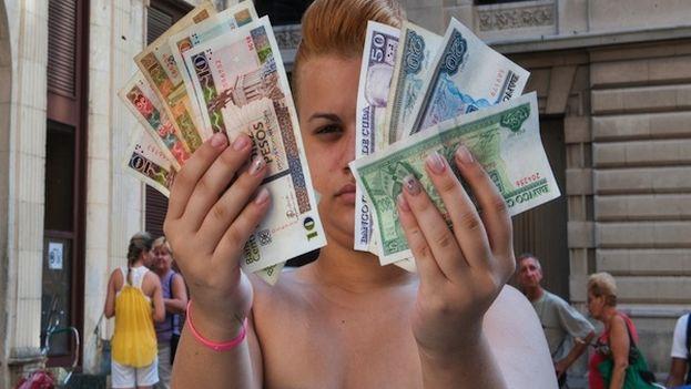 Una mujer muestra algunos billetes de CUC y CUP en La Habana. (Cubanet)