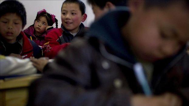 Unos niños chinos realizan sus deberes en la escuela. (EFE)