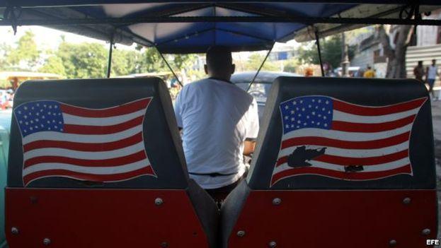 Un hombre conduce por las calles de La Habana un bicitaxi con la bandera de Estados Unidos. (EFE)