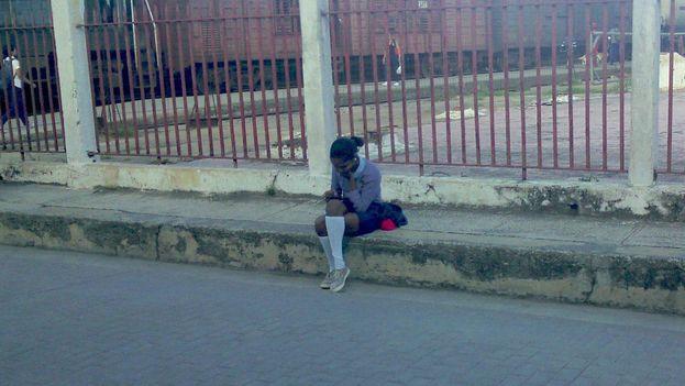 Una joven se conecta a una red wifi informal en la calle República de la ciudad de Camagüey. (14ymedio)