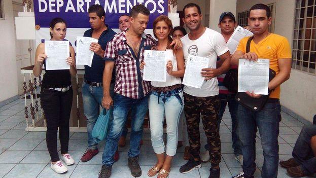 Un grupo de cubanos muestra el oficio de salida que recibieron hoy en Tapachula, México.