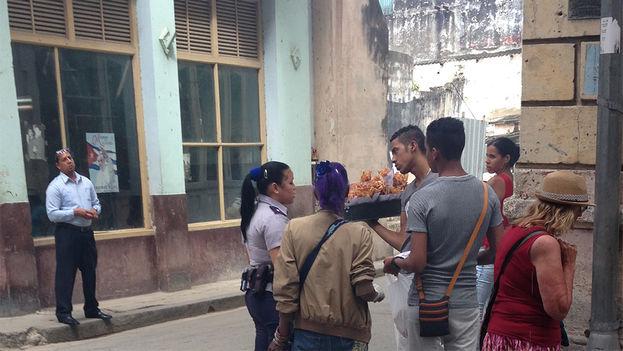 Una policía pide los documentos a un vendedor ambulante de alimentos en una calle de La Habana Vieja. (14ymedio)