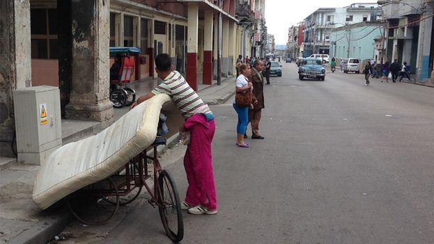Un hombre coloca un colchón sobre una bicicleta en una calle de La Habana. (14ymedio)