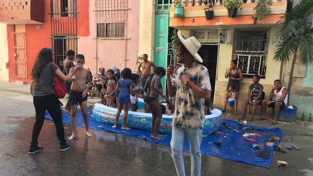 Desde una piscina improvisada varios niños reciben a Raymel con tanta excitación que él mismo acaba empapado. (14ymedio)