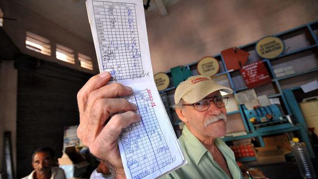 Un hombre muestra la libreta de racionamiento por la que recibe parte de la canasta básica mensual. (EFE)