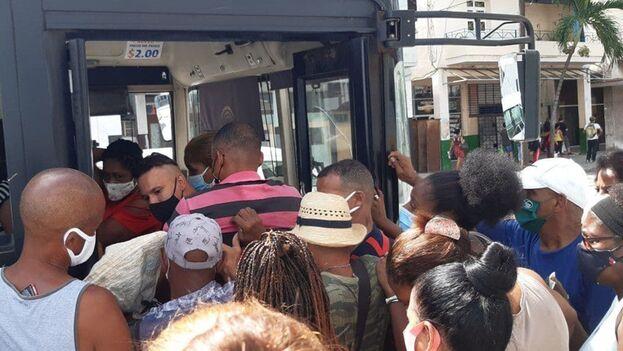 Un grupo de personas en la capital cubana forcejeando para intentar subirse a una guagua este 16 de agosto de 2021. (14ymedio)