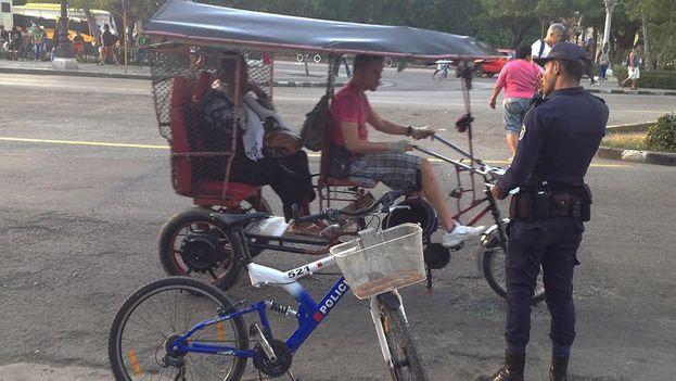 Un policía controla los papeles de un bicitaxista en La Habana. (14ymedio)