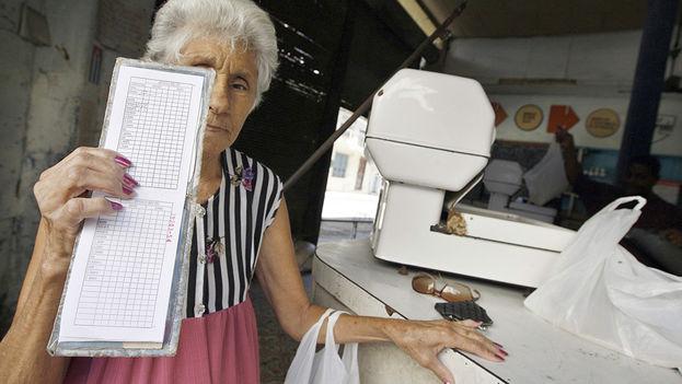 Una anciana muestra la cartilla de racionamiento que cada año tiene menos productos subsidiados por el Gobierno. (EFE)