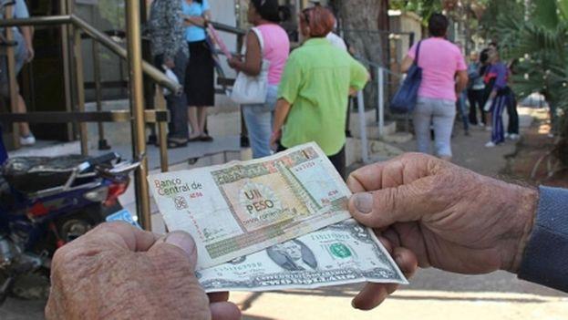Un hombre sostiene unos billetes de dólar y pesos convertibles frente a una Caja de Cambio. (EFE)