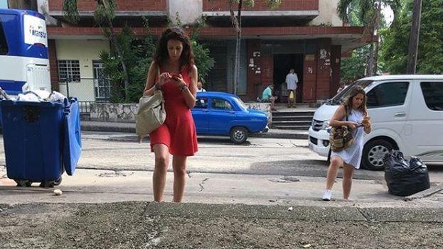 Dos mujeres miran sus teléfonos mientras caminan en La Habana. (Luz Escobar)